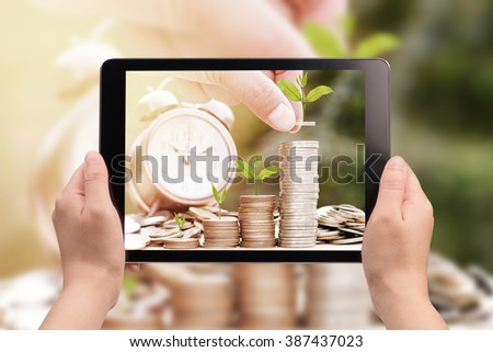 hand holding digital tablet with a picture of hand stacking coins with green plant ,Business Finance and Money concept,Save money for prepare in the future.