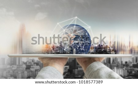 Hand holding digital tablet with global network connection technology and modern buildings. Element of this image are furnished by NASA #1018577389