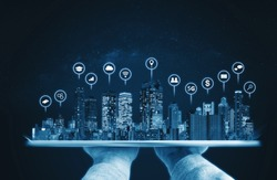 Hand holding digital tablet with modern buildings hologram and technology icons. Smart city, internet and networking smart technology