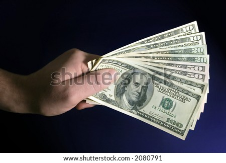 hand holding dollars in blue background.