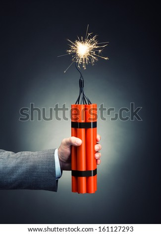 Hand holding dynamite with burning wick