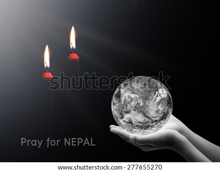 Hand holding earth and candle on black background , Pray for nepal , Elements of image are furnished by NASA