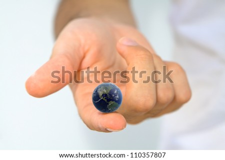 Hand holding earth on fingertip/ World at your Fingertips (Elements of this image furnished by NASA)