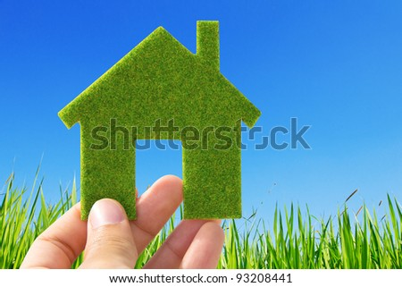 Hand holding eco house icon on nature background