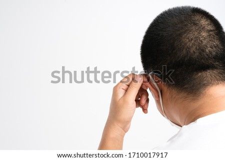 Hand holding elastic ear loop of medical mask as hurting ear gesture on white background