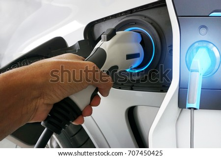 Hand holding Electric car charger. Power supply electric car charging for electric car technology transportation.