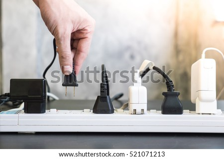 Hand holding electric plug, Multiple socket with connected plugs. Foto stock ©