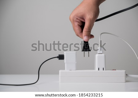 Hand holding Electric plug put on multiple socket. Electrical equipment, electrical wires and power strips in the house. Earth Hour saving electrical energy.