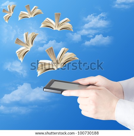 Hand holding electronic book and opened books flying to the sky (education concept)