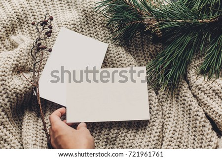 hand holding empty christmas cards or wish list on stylish simple knitted sweater with fir  for christmas holidays. eco design. xmas seasonal greetings mock up. letter to santa claus