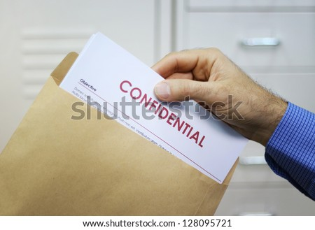 Hand holding envelope with top secret confidential documents
