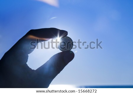 Hand holding Euro coin against blue sky
