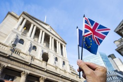Hand holding European Union and British Union Jack flag in front of the Bank of England as symbols of the financial repercussions of the Brexit EU referendum