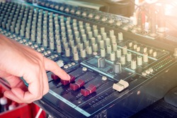 Hand holding faders of the mixing audio on desk for music with lighting effect,entertainment themes