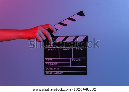 Hand holding film clapper board in blue red neon light. Cinema industry, entertainment.