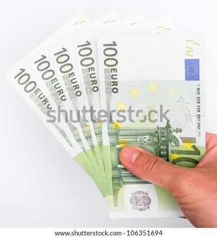 Hand holding five hundred euro bills on white background