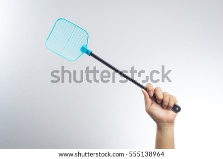 hand holding fly or insect swatter on white background - Shutterstock ID 555138964