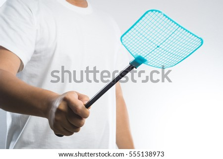 hand holding fly or insect swatter on white background - Shutterstock ID 555138973