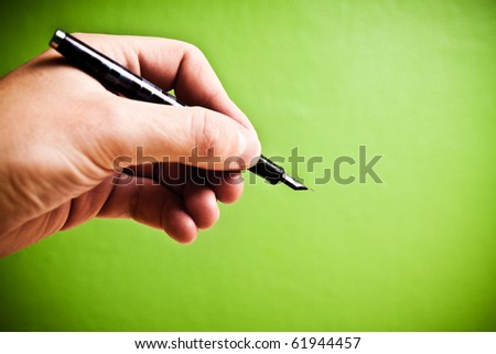 Hand holding fountain pen on green background