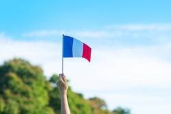 hand holding France flag on blue sky background. holiday of French National Day, Bastille Day and happy celebration concepts