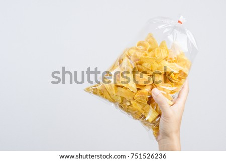 Hand holding fried sliced banana chip in food plastic bag tied by rubber on white background #751526236