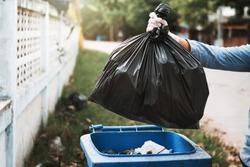hand holding garbage black bag putting in to trash
