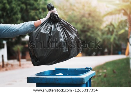 hand holding garbage black bag putting in to trash Stock photo ©