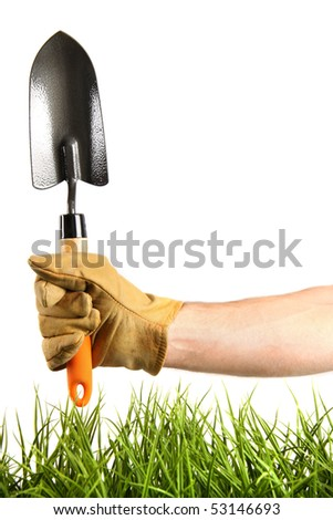 Hand holding garden trowel on white