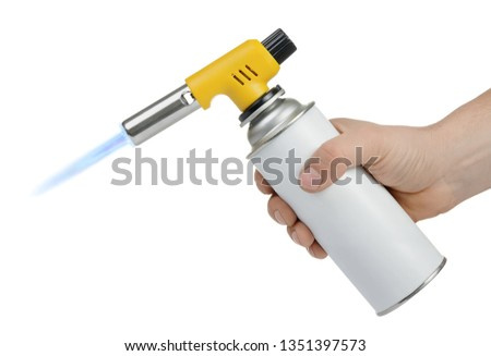 Hand holding gas can with manual torch burner (blowtorch) with blue flame isolated on white background. Serie of tools. #1351397573