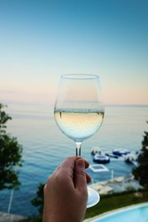 Hand holding glass of vine over the sea and swimmingpool