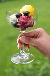 Hand holding glass with sweet dessert special Thai ice-cream made from strawberry and cream with fruit