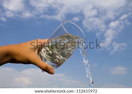 Hand holding glass with water pouring down