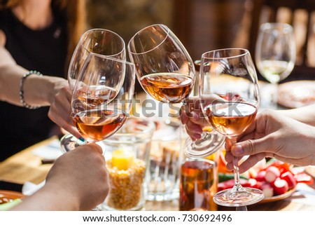 Hand holding glasses with rose wine over a table rich with Balkan and Moldovan cuisine dishes #730692496