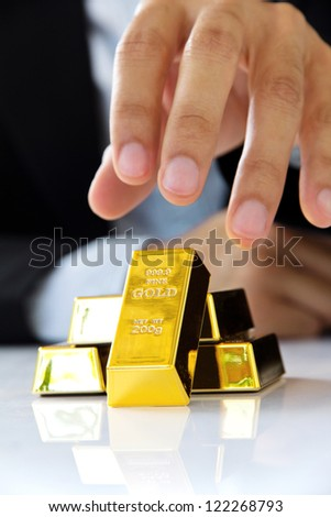 hand holding gold bars