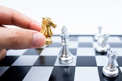 Hand holding gold horse attack silver king in battle on chess board.Business leader concept for market target strategy.Intelligence challenge and business competition success play.Symbol of winner