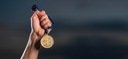 Hand holding gold medal on against cloudy twilight sky background, The winner and successful concept