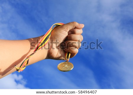 hand holding gold medal on blue sky