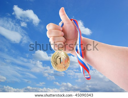 Hand holding gold medal on sky background