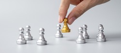 hand holding golden chess pawn pieces or leader businessman with of silver men. victory, leadership, business success, team, recruiting, and teamwork concept