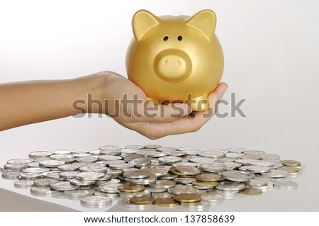 Hand holding golden piggy bank with stack of coin