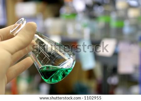 Hand Holding Graduated Cylinder - stock photo