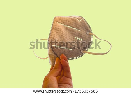Hand holding gray KN95 or N95 mask .Anti pollution mask.air face mask.KN95 or N95 mask with N95 word.n95 on yellow background .