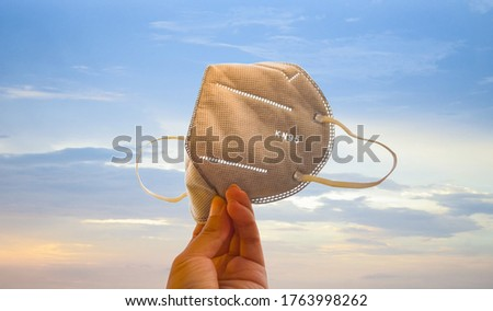 Hand holding gray KN95 or N95 mask for protection pm 2.5 and corona virus (COVID-19).Anti pollution mask.air face mask.KN95 or N95 mask with N95 word.n95 on blue sky background .