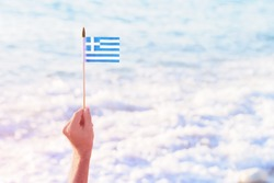 Hand holding Greek waving flag flying over sea water waves. Travel to Greece or national Day. Copy space