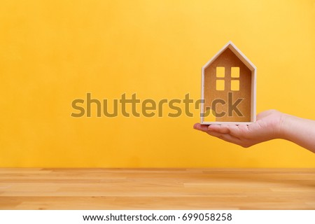 Hand holding home model with wooden table and yellow background for house ownership or real estate business concept #699058258