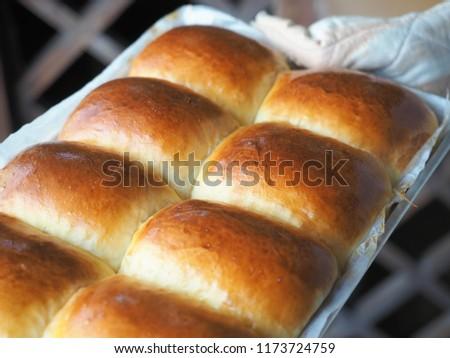 hand holding hot baking tray of bread rolls
