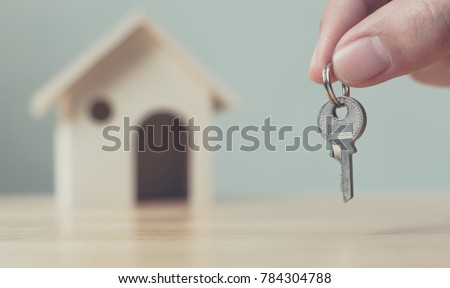 Hand holding house key with wooden home background blurred, Real estate and property investment and house mortgage financial concept