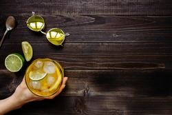 Hand holding ice drink. Ice tea, lemon, lime and sunglasses on the wooden table, top view. With copy space.