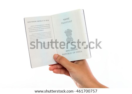 Hand holding Indian passport open against white background