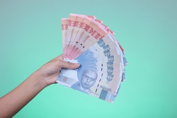 Hand holding Indonesian currency, 100,000 and 50,000 rupiah banknotes with cyan background